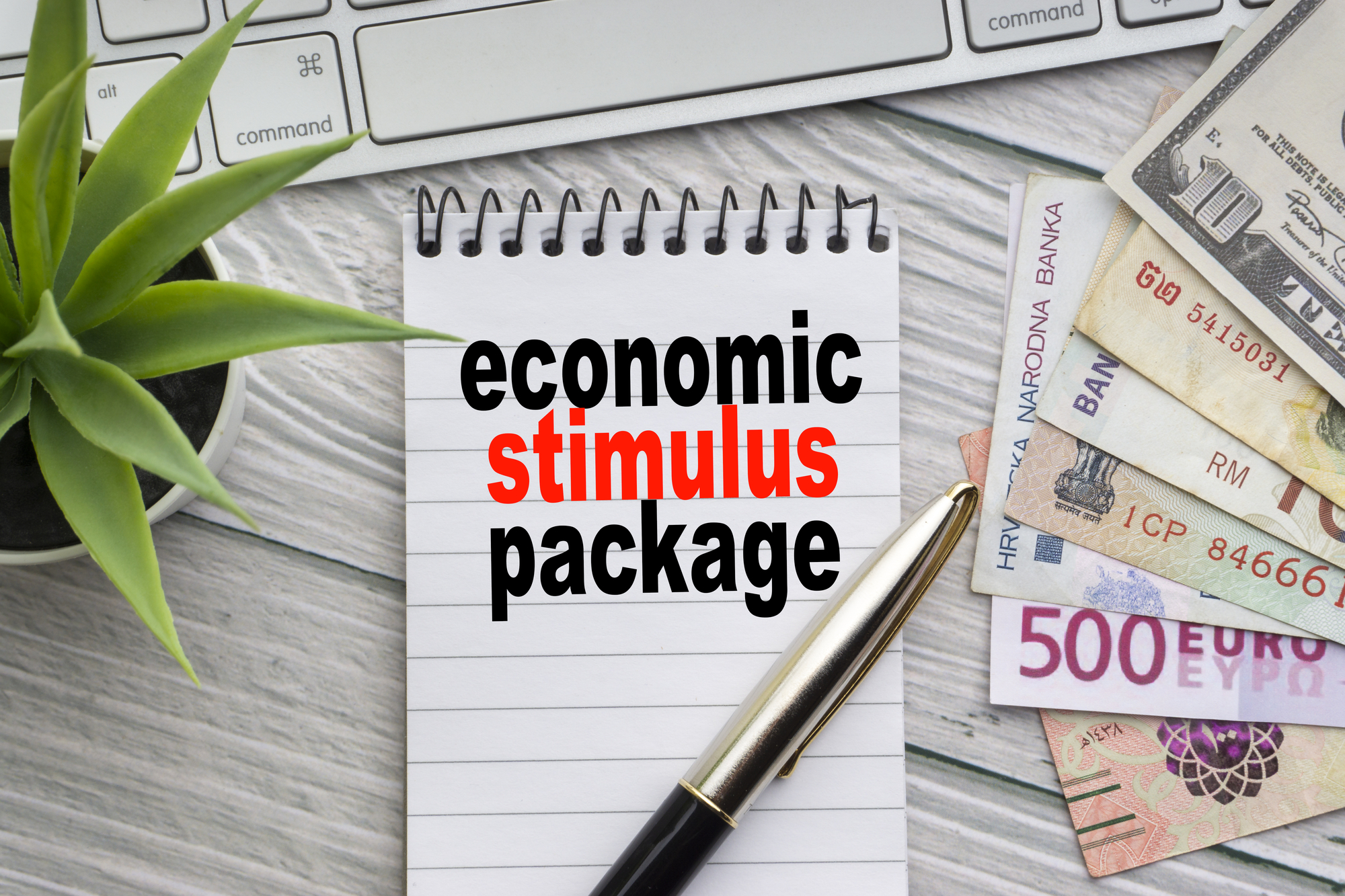 ECONOMIC STIMULUS PACKAGE text with notepad, keyboard, decorative vase, fountain pen, calculator and banknotes currency on wooden background
